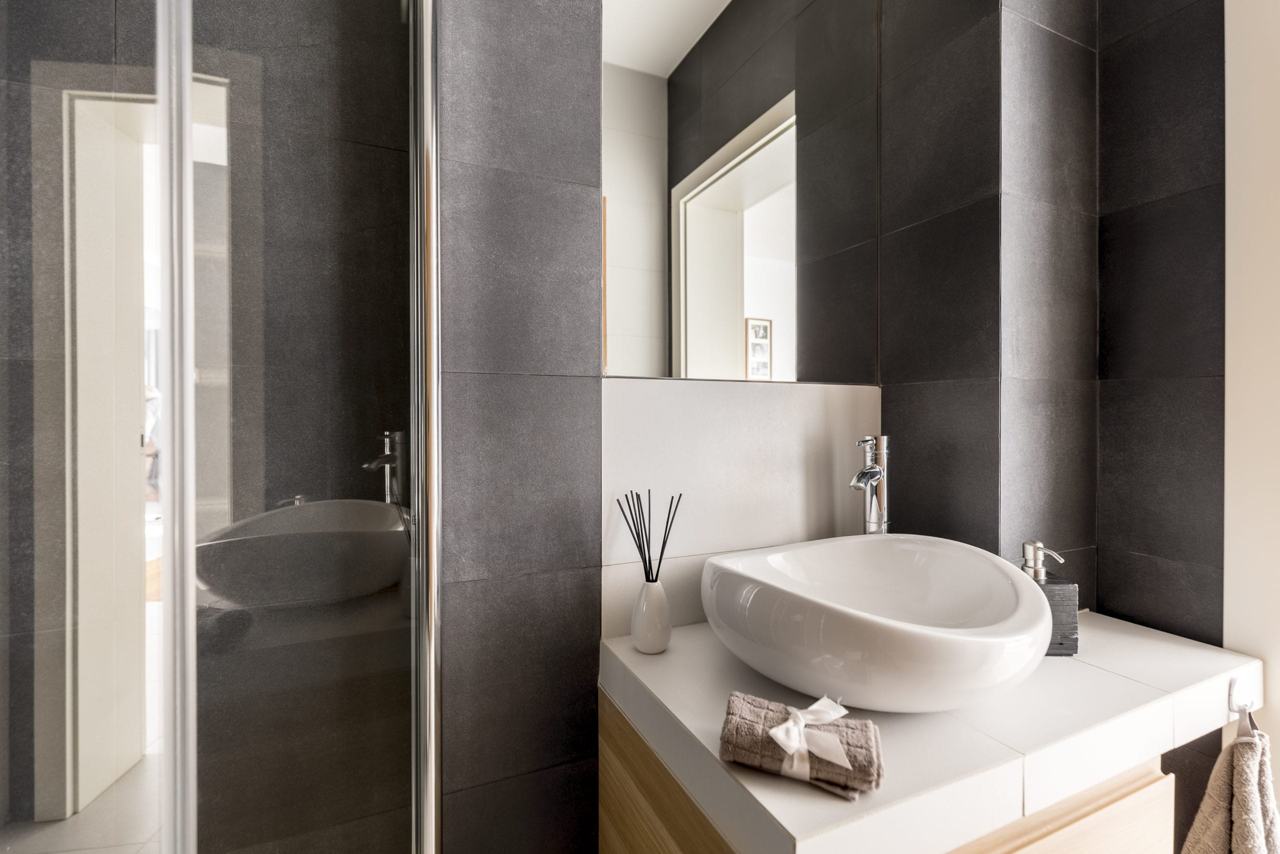 Grey bathroom with white washbasin and mirror